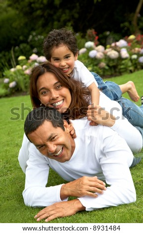 family lifestyle portrait of a mum and dad with their kid having fun outdoors - stock photo