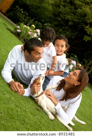 family lifestyle portrait of a mum and dad with their two kids having fun outdoors - stock photo