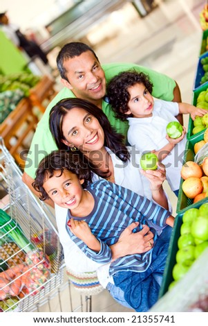 Family lifestyle portrait of a mum and dad with their two kids shopping in supermarket - stock photo