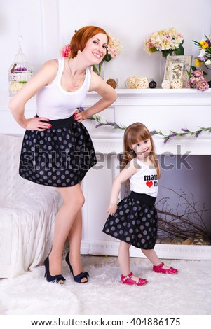 Family look. Beautiful young mother and her cute little daughter are looking at camera and smiling, - stock photo
