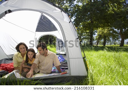 Family looking at map in tent