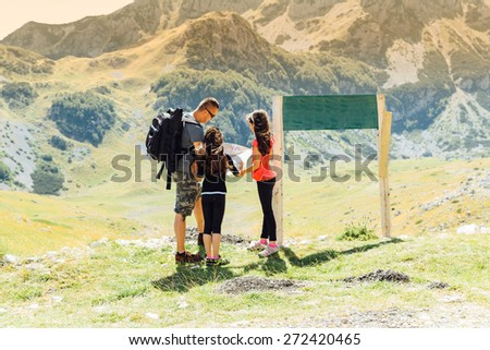 Family looking at map on near national park sign a hiking day.Happy family in mountains discussing the route.Family on mountain trek.  - stock photo