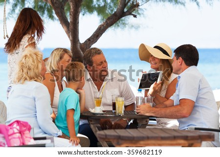Family looking at photo on touch pad in outdoor cafe - stock photo