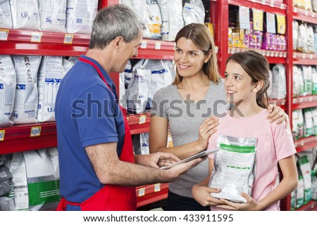 Family Looking At Salesman Using Digital Tablet In Pet Store - stock photo