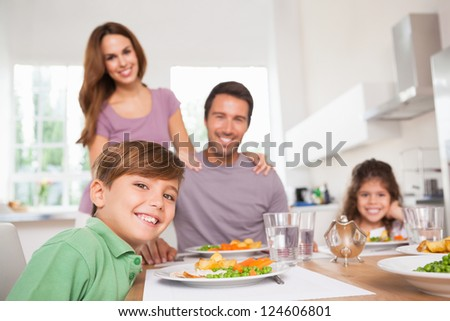 Family looking at the camera at dinner time in kitchen - stock photo