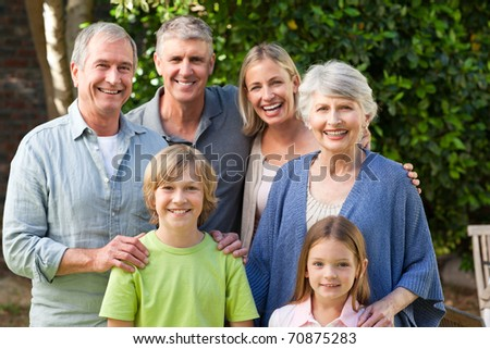 Family looking at the camera in the garden - stock photo
