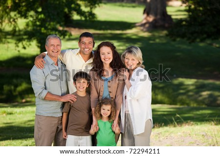 Family looking at the camera in the park - stock photo
