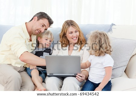 Family looking at their laptop at home
