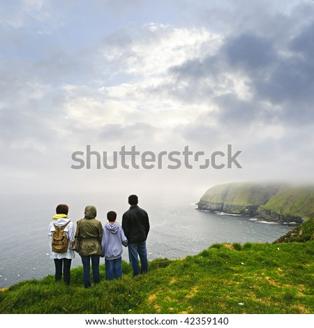 Family looking from cliff at Cape St. Mary's Ecological Bird Sanctuary in Newfoundland, Canada - stock photo