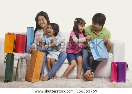 Family looking inside shopping bags - stock photo
