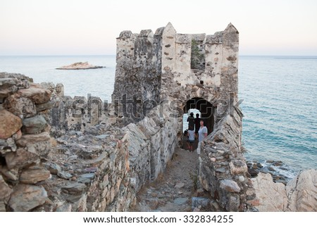 Family looking medieval fortress. Maumere fortress and sea near Anamur, Turkey - stock photo