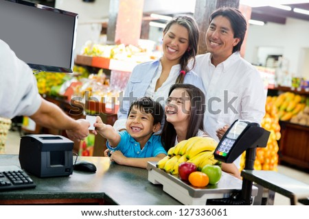 Family looking out for home finances at the supermarket - stock photo