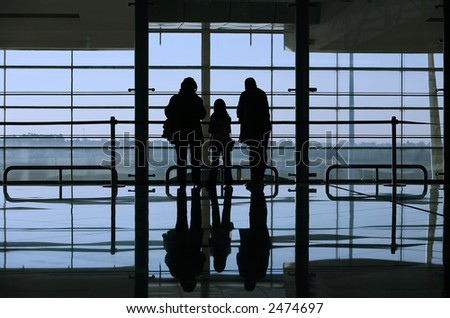 family looking through the window in the airport - stock photo