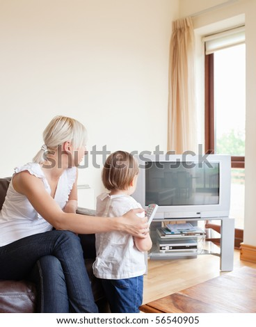Family looking to the television in the living room - stock photo