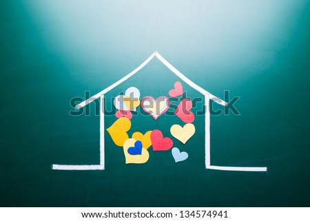 Family love concept, drawing house and colorful heart shape on blackboard - stock photo