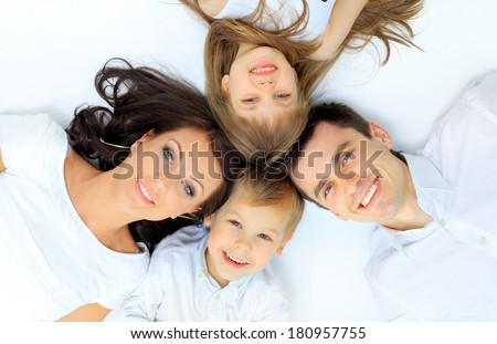 Family lying down on their bed at home - stock photo