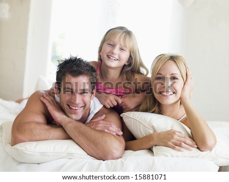 Family lying in bed smiling - stock photo