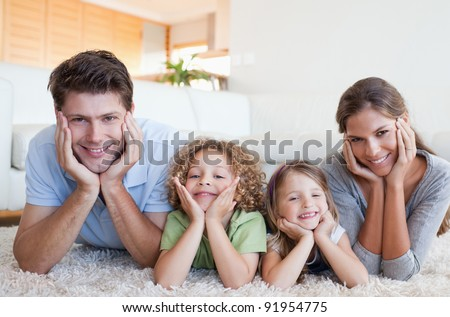 Family lying on a carpet in their living room - stock photo