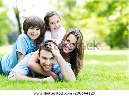 Family lying on grass - stock photo