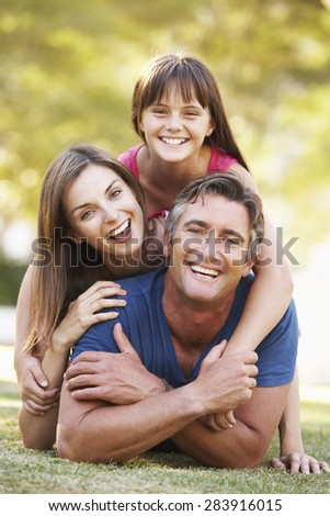 Family Lying On Grass In Summer Park - stock photo