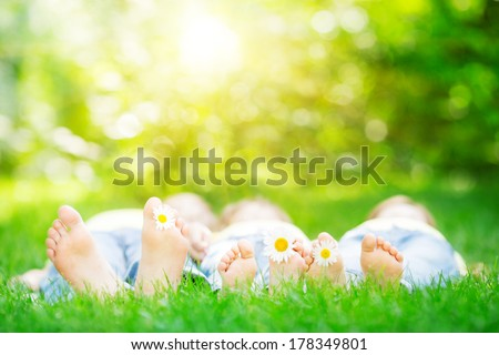 Family lying on grass outdoors in spring park - stock photo