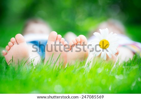 Family lying on green grass. Children having fun outdoors in spring park - stock photo
