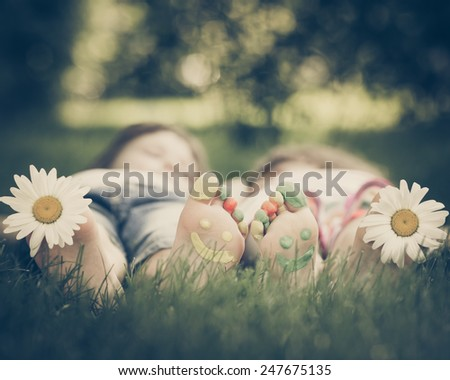 Family lying on green grass. Children having fun outdoors in spring park. Retro toned image - stock photo
