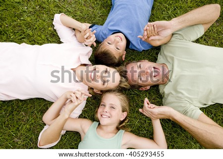 family lying on ground holding hands in a star shape