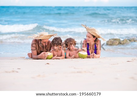 Family lying on the beach and drinking coconut milk