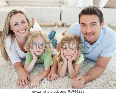 Family lying on the carpet together - stock photo
