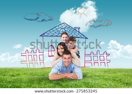 Family lying on top of each other against blue sky over green field - stock photo