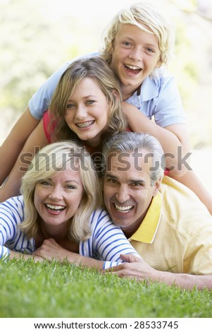Family Lying On Top Of Each Other In A Park - stock photo
