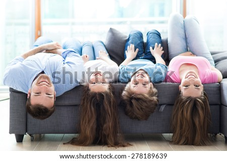 Family lying upside down on sofa  - stock photo