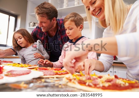 Family making pizza together - stock photo