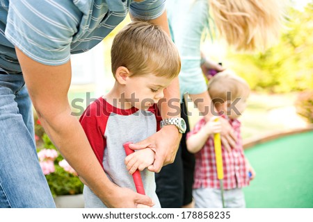 Family: Man Helps Child Hold Putter For Mini-Golf - stock photo
