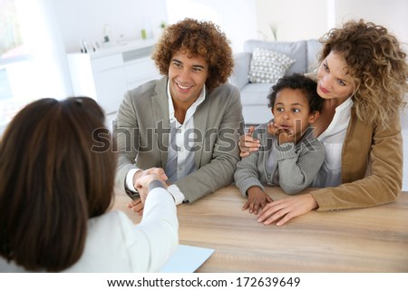 Family meeting real-estate agent for home purchase - stock photo