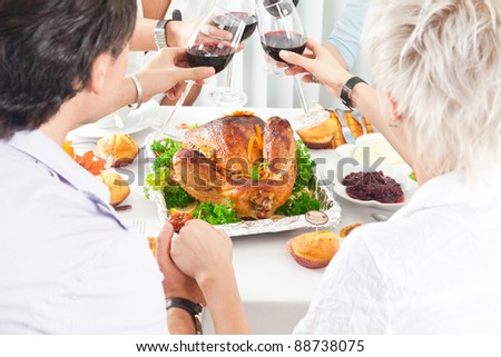 Family members giving thanks to God at festive table while holding each other by hands, close-up - stock photo