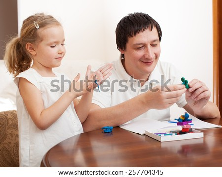 Family molded from clay toys. Father play with girl - stock photo