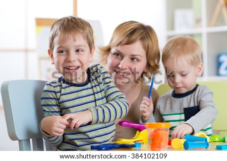 Family molded from clay toys. Mother play with children. - stock photo