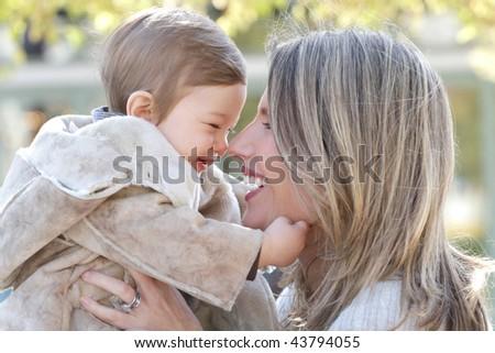 Family: mother and baby son having fun outdoors, city street setting, fall seasonal theme - stock photo