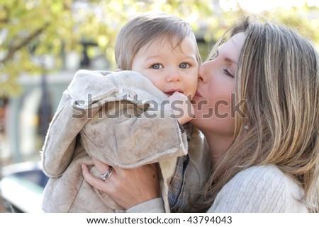Family: mother and baby son having fun outdoors, city street setting, seasonal, fall theme - stock photo
