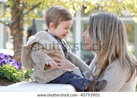 Family: mother and baby son outdoors, city street setting - stock photo