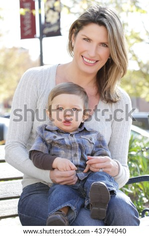 Family: mother and baby son sitting on a bench in a city, street setting - stock photo