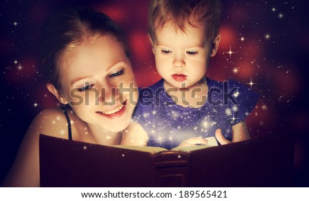 family mother and child baby daughter reading magic book in the dark - stock photo