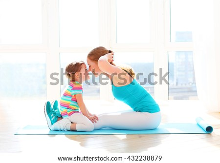 family mother and child daughter are engaged in fitness, yoga, exercise at home - stock photo