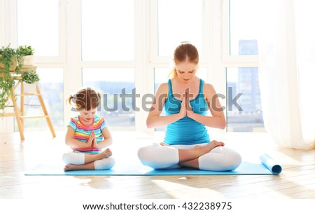 family mother and child daughter are engaged in meditation and yoga, exercise at home - stock photo