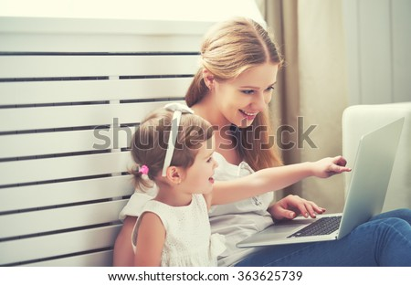 family mother and child daughter at home with a laptop - stock photo
