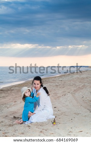 family mother and daughter on a sandy beach under a cloudy sky