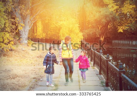 Family mother and daughter walking in the park in autumn - stock photo