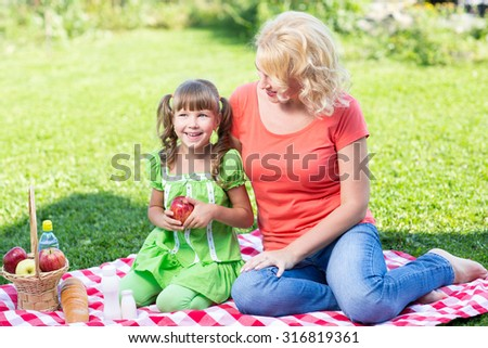 Family mother and little daughter having picnic in summer park